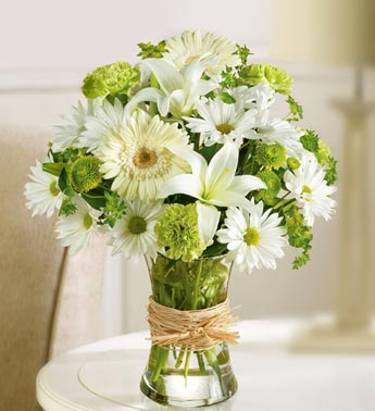 green and white flowers in clear vase