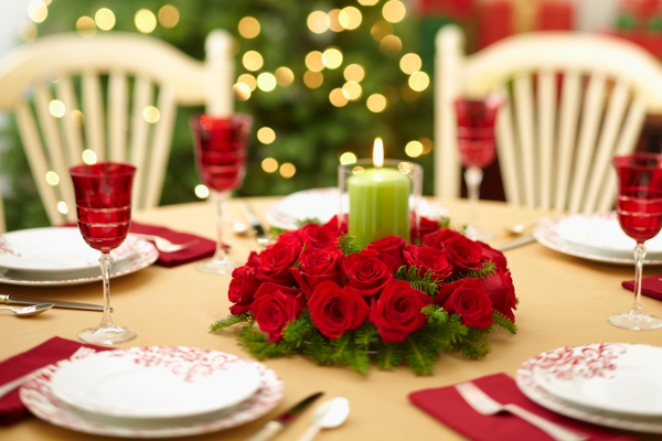 Christmas table centerpiece with red roses and evergreens