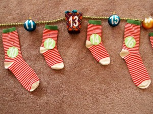 Christmas Ornaments and Socks Strung up on Garland to Make an Advent Calendar