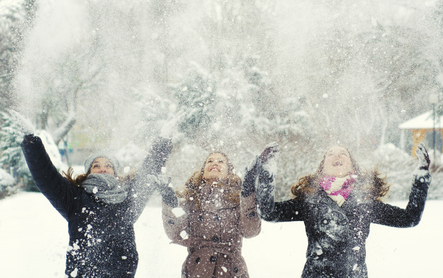 Girls throwing snow in the air