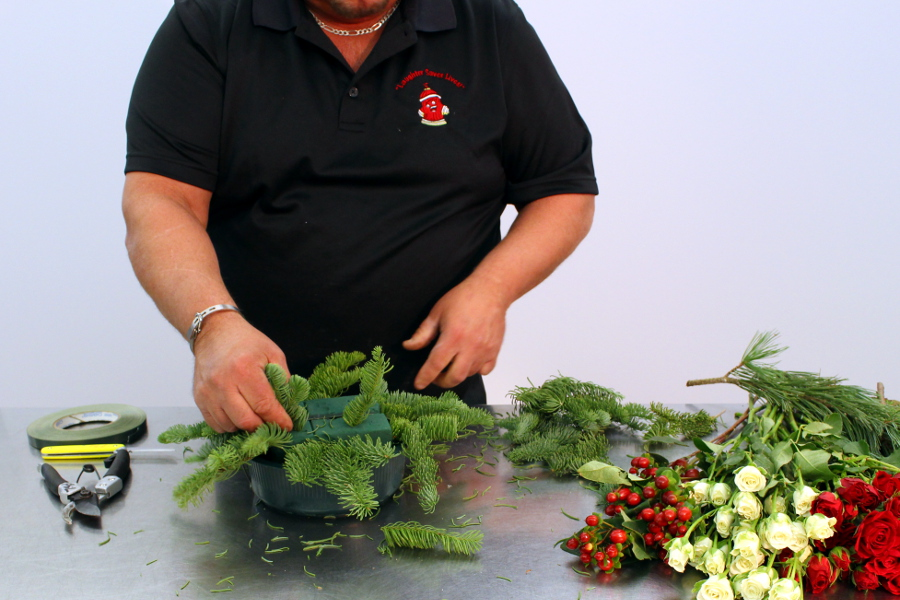 Insert Christmas greens into floral foam