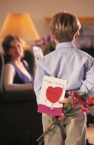 Boy giving hand-made card and flowers to mom
