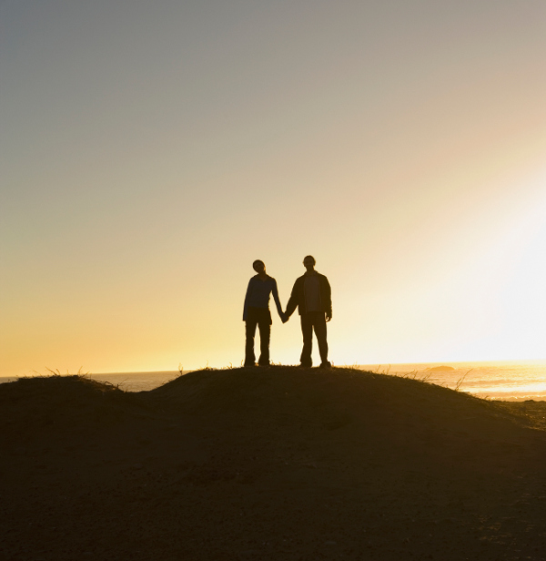 Silhouette of couple hiking standing on a hill
