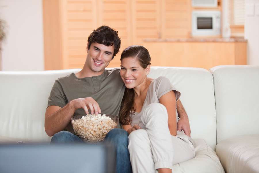 Couple watching a movie at home with popcorn