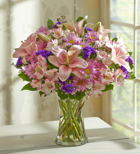 Flower arrangement with pink lilies, alstroemeria, daisies and purple accents