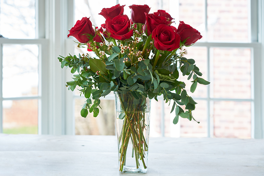 Red roses arranged in a vase.