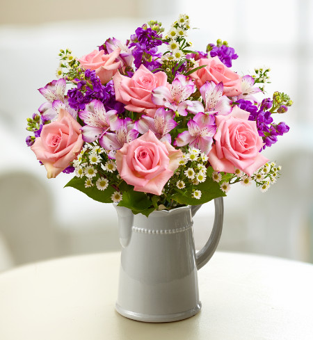 Bouquet in water pitcher with pink roses, alstroemeria and purple statice