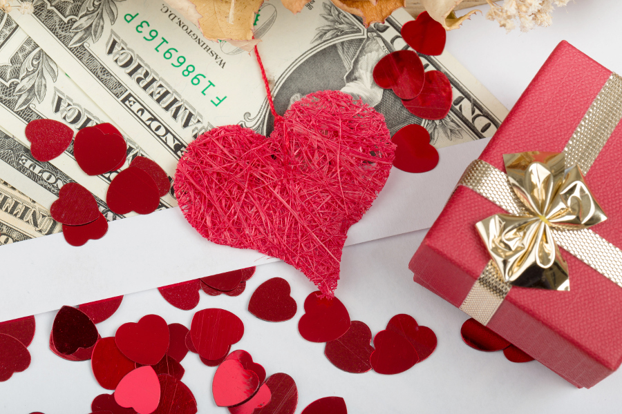 Red heart and red box on top of dollar bills