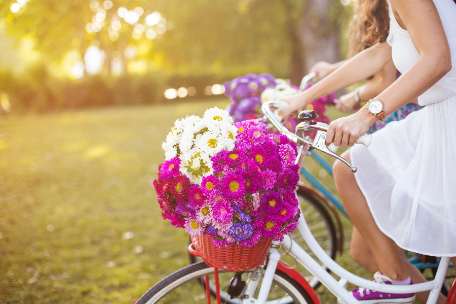 Woman on a bicycle with a basket full of flowers