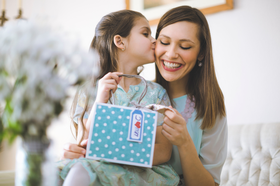 Girl giving mom birthday gift and kissing her on the cheek