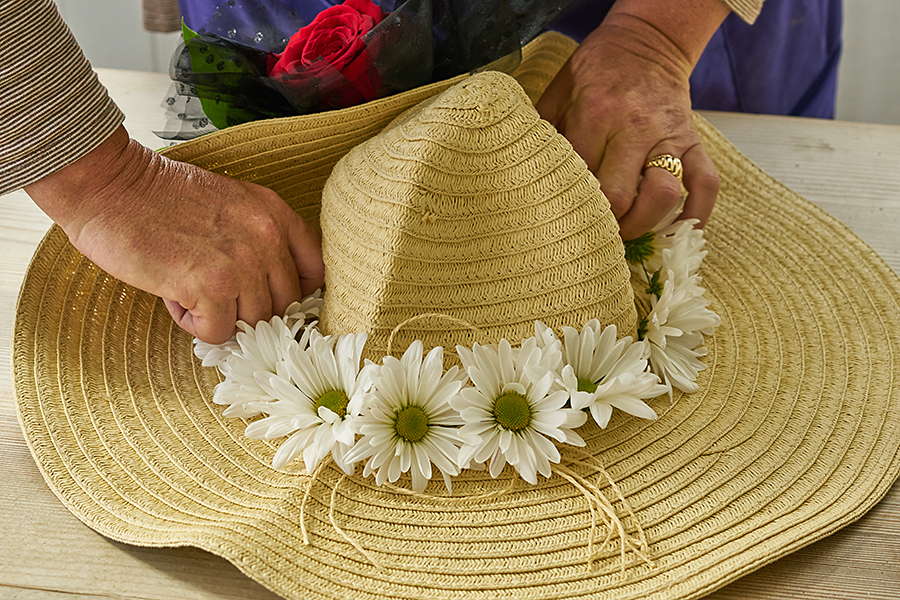 Glue flowers onto brim of hat