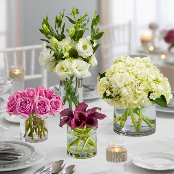 Wedding flower centerpieces, purple roses, purple calla lilies, white roses, white hydrangea