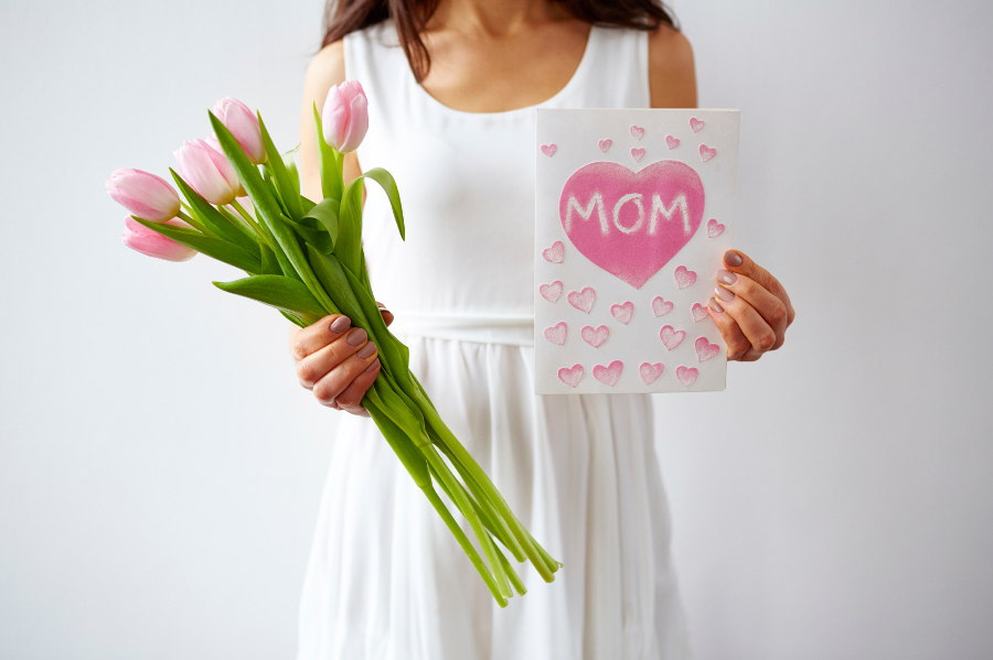 Woman holding pink tulips and handmade Mother's Day card