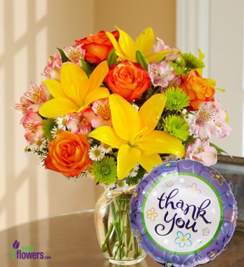 Yellow lilies, orange roses, peruvian lilies, in a clear glass vase with thank you balloon
