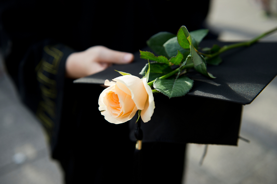 graduation gown and cap with white rose