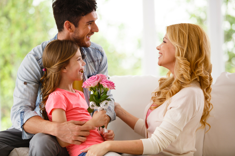 daughter-and-father-giving-mom-flowers-for-birthday