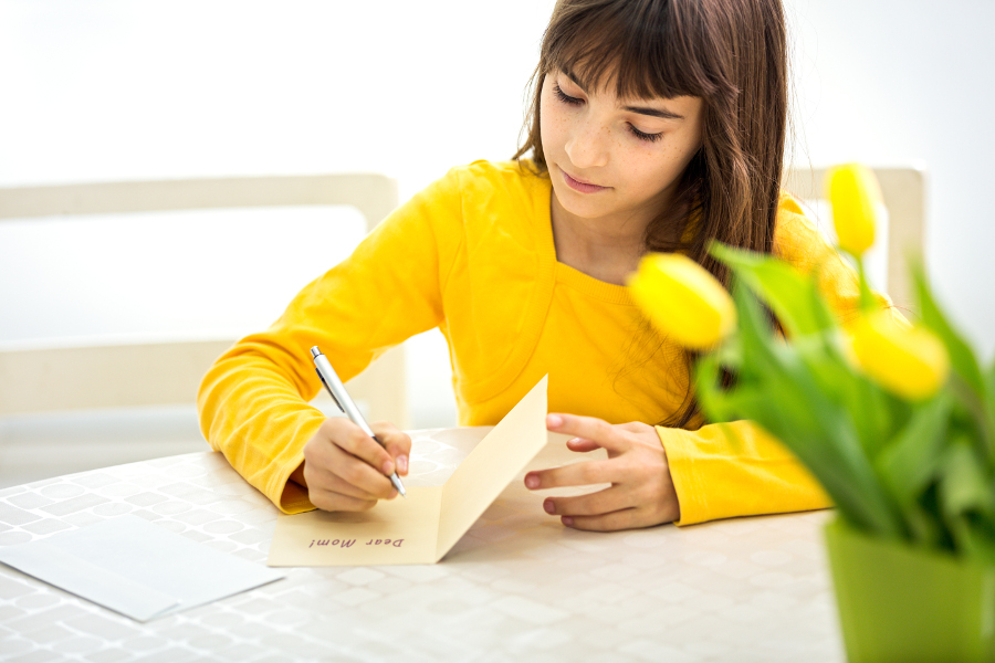 girl writing a card for her mom