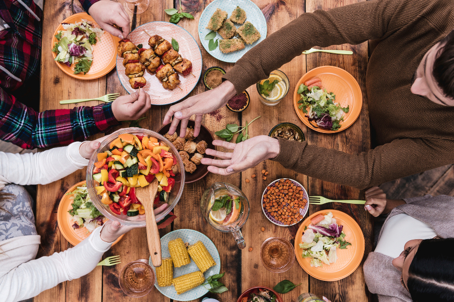 People passing food over Thanksgiving table