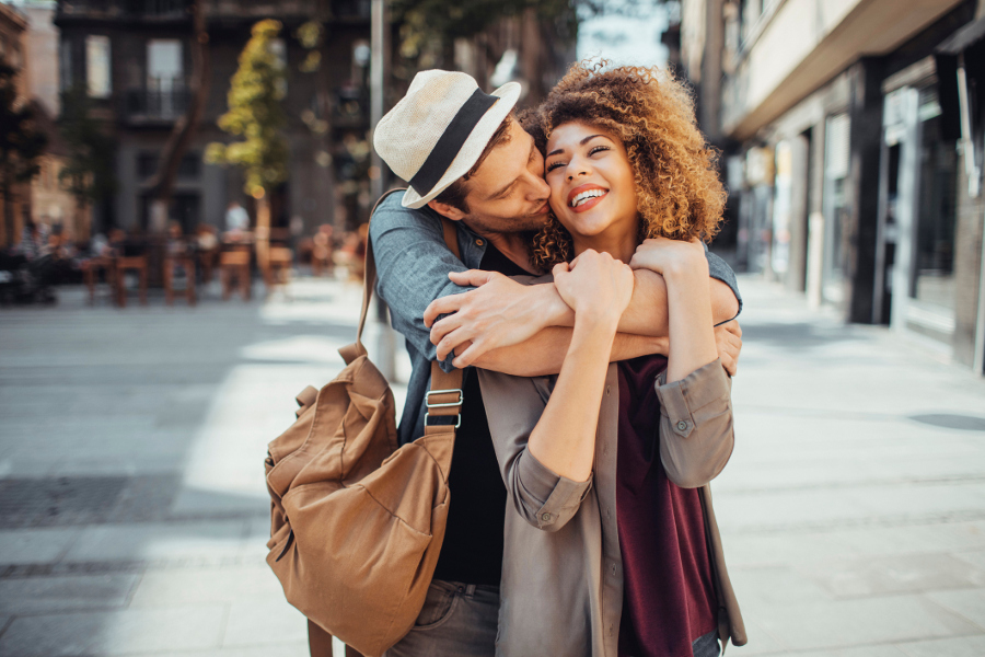 Couple hugging from behind with a kiss
