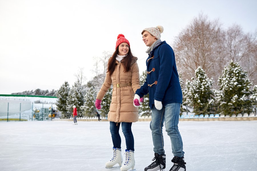 Couple holding hands while ice skating