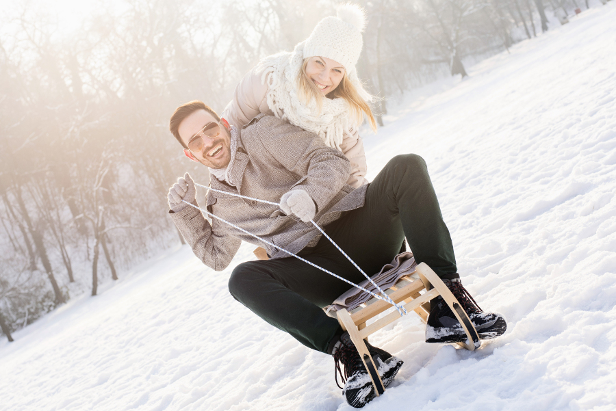 Couple Sledding in Winter Snow