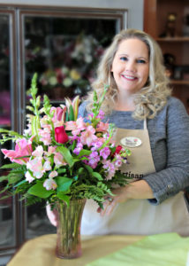 Florist Develyn Reed posing with floral arrangement