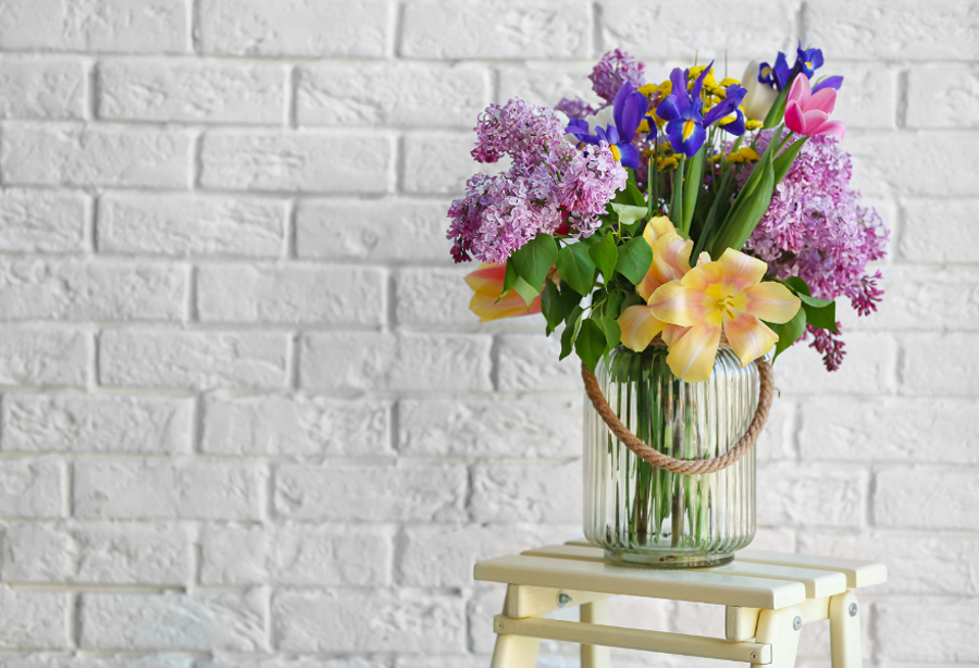 Flowers in vase against brick background