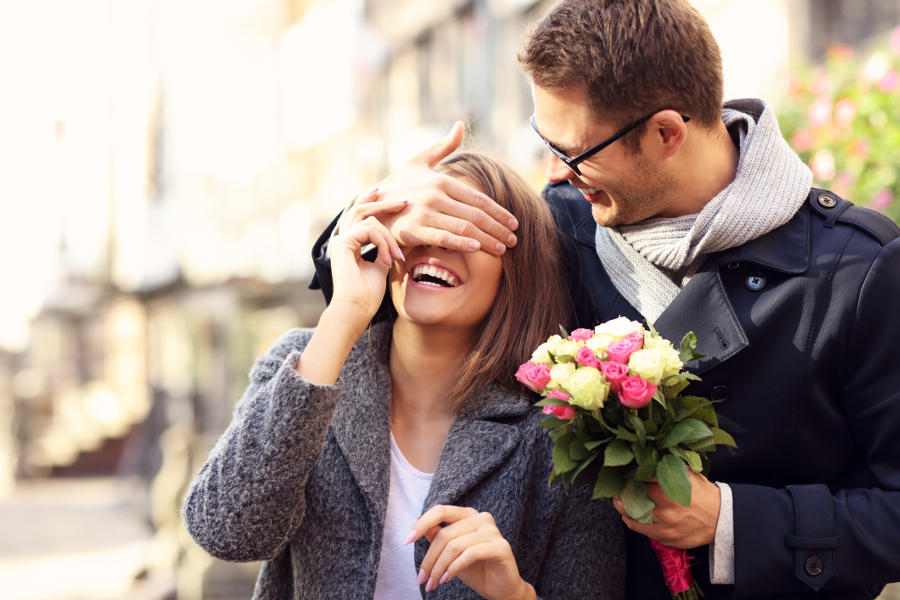 Young man surprising woman with flowers