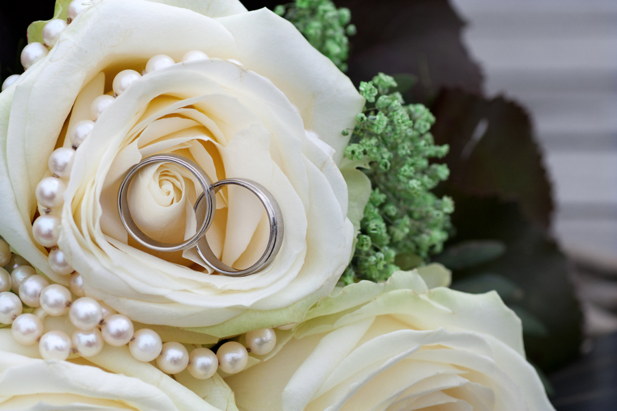 Wedding rings presented in a bouquet of white roses