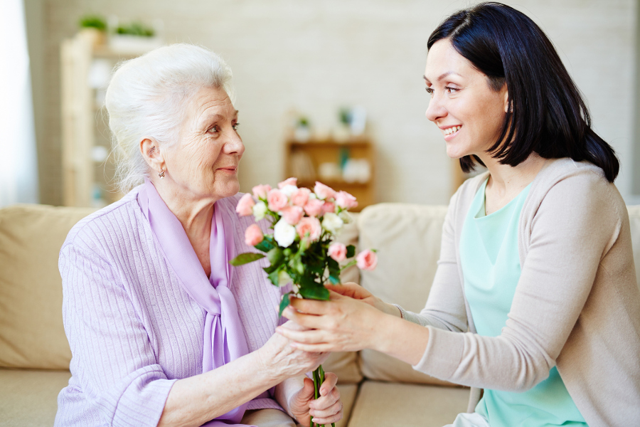 Woman giving her mom flowers for parents day