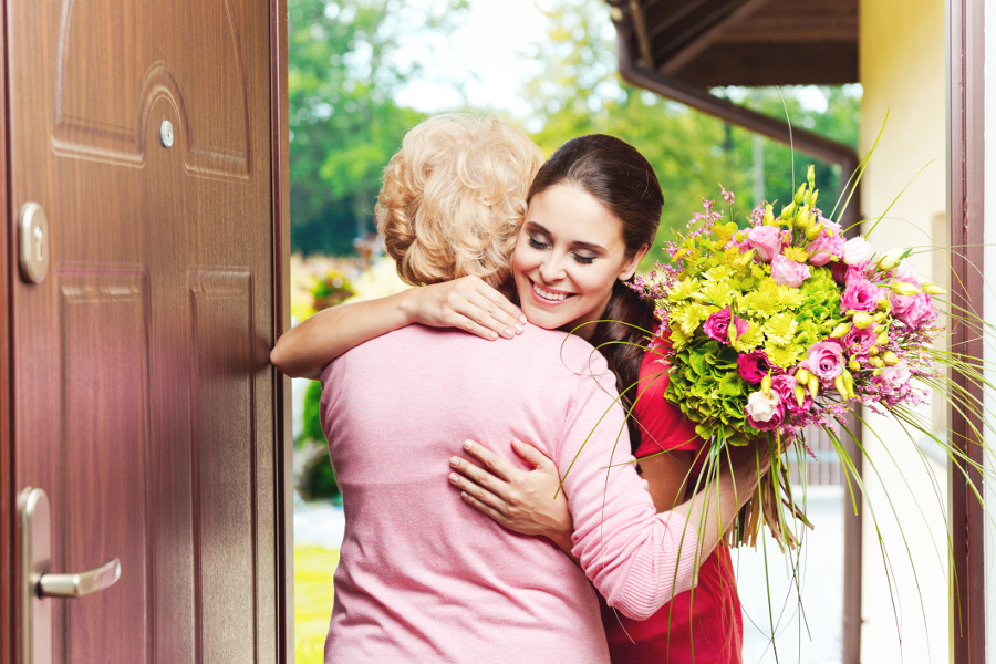 Woman giving flowers to grandmother