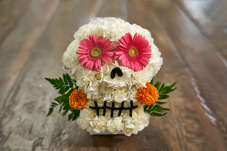 white flower skull with pink flower eyes with marigold flowers