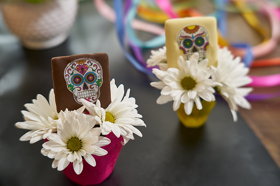 chocolate sugar skull treats inside white flower holders