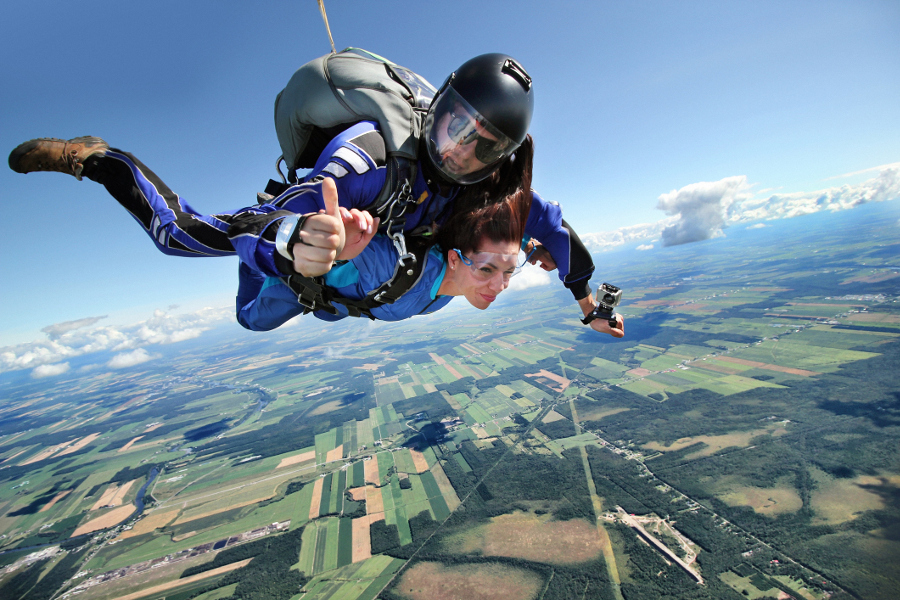woman skydiving giving thumbs up