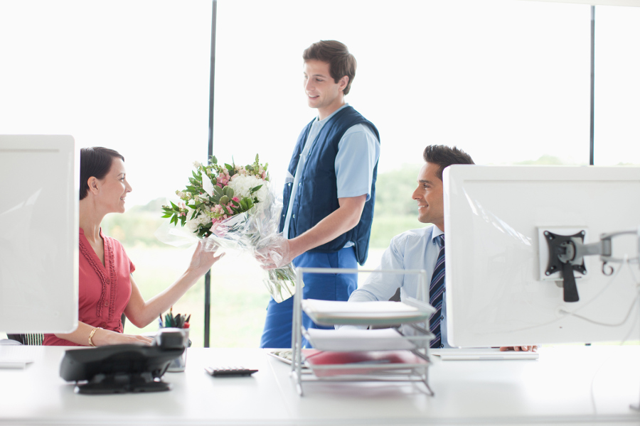 man delivering flowers to woman in an office