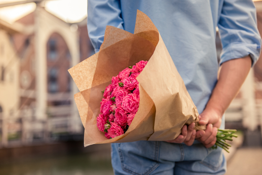person holding flowers behind back