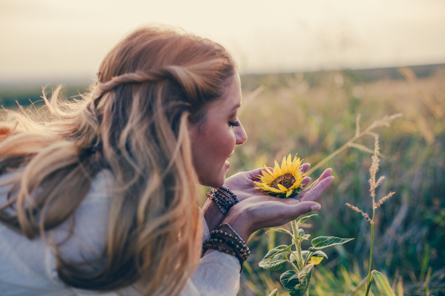 woman smelling sun flowers