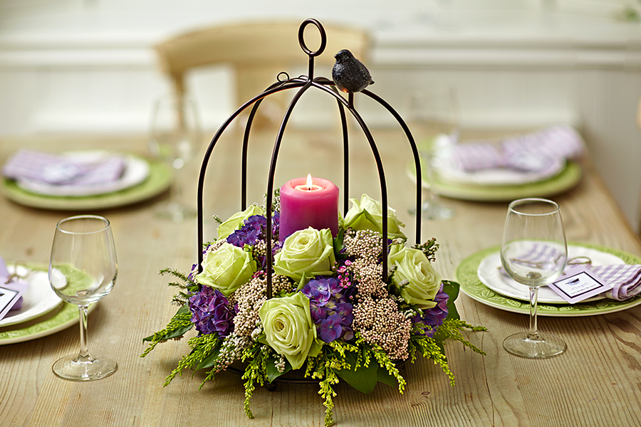 Bird cage centerpiece with flowers and candle
