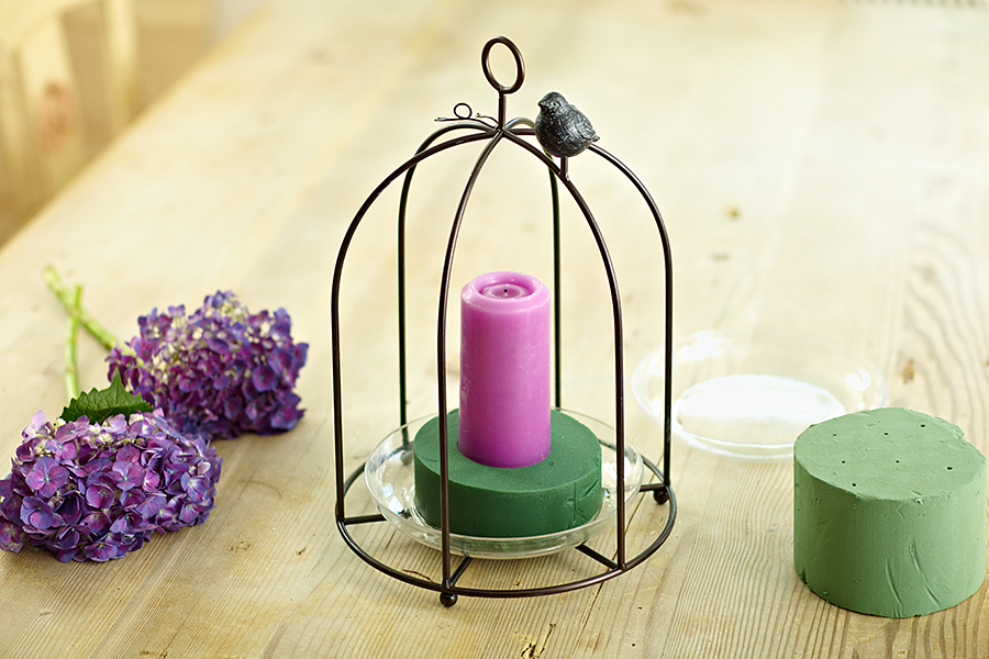 Bird cage centerpiece with purple candle placed on foam piece