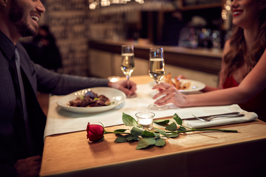 Couple having dinner with champagne and red rose