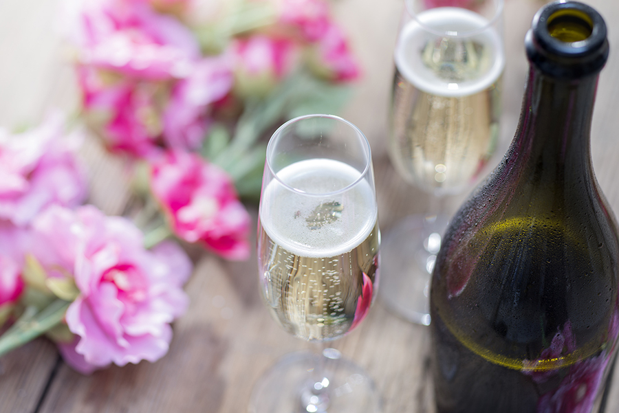 Bottle of Prosecco and two champagne glasses on a rustic garden picnic table with blossom or flowers in the background. Springtime or Summertime.