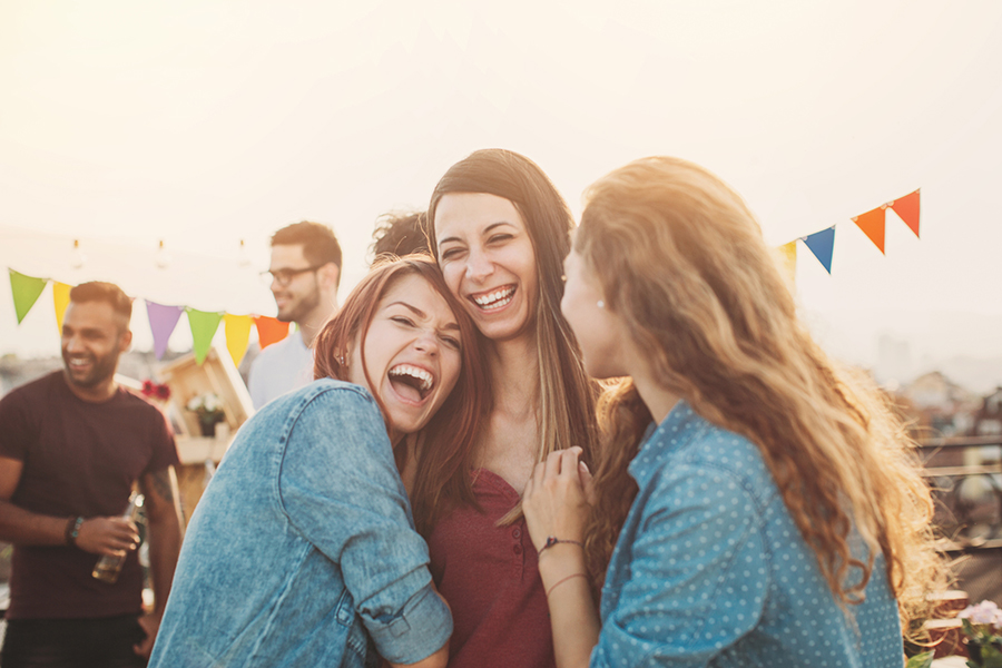 Three girls holding and laughing loud on a rooftop party.