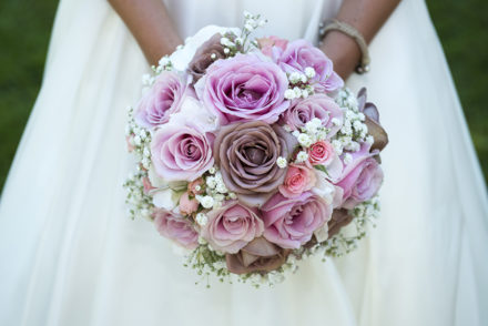 Close-up photo from a bride holding her pink wedding bouquet