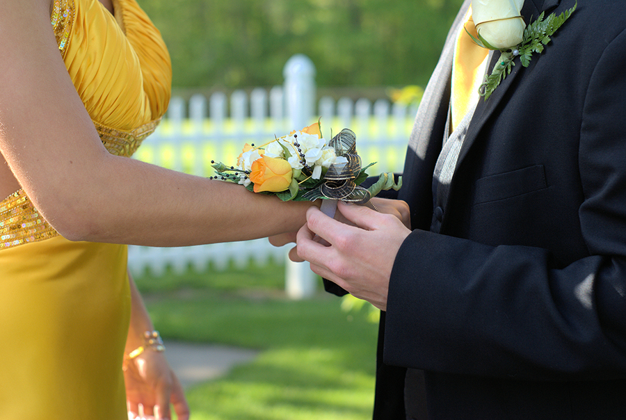 man placing flowers on woman's wrist for prom