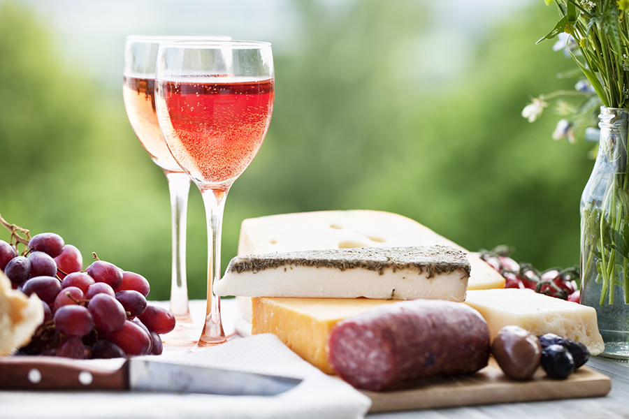 rose wine and cheese with sausage and grapes outdoors