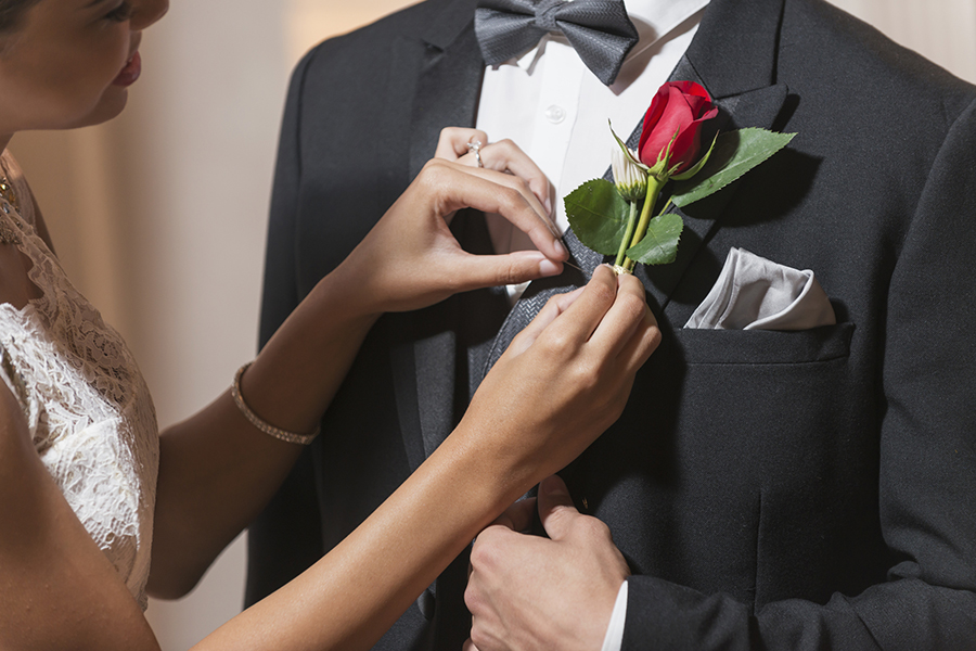 Cropped view of a teenage couple wearing formal attired, going to the prom or other special formal event. The mixed race young woman is pinning a boutonniere on her date's lapel.