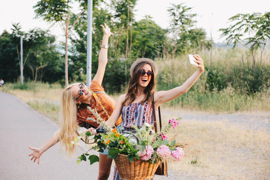Two best friends riding a bike with flowers in the basket taking a selfie