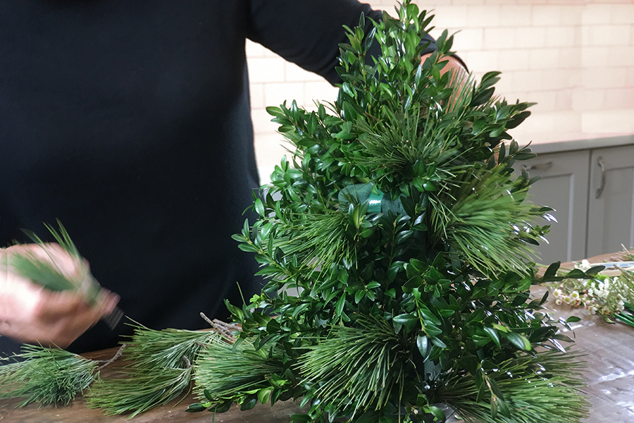 Add evergreens to holiday flower tree
