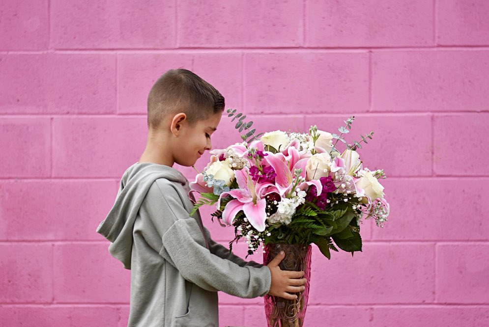 boy giving bouquet to mom