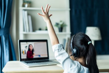 Girl raising hand at laptop